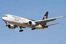 Side quarter view of UPS twin-engine freighter in flight, with extended gear
