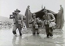 Black and white photo of three men wearing military uniforms and carrying guns and bags wading through water in front of a boat