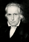 A middle-aged, studious looking man with white hair and old-fashioned glasses pushed up over his head. He is looking almost directly towards the viewer, with his shoulders turned slightly towards the left. He is wearing a dark coat and a white shirt with a broadly spread collar.