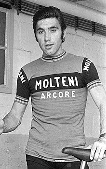 """Merckx holding a bicycle. His shirt says """"Molteni Arcore"""", and his hair is slicked back."""