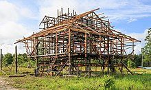The wooden frame of a house under construction, with the floor raised off the ground
