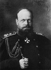 A stocky, balding man with a beard, wearing a dark military uniform.