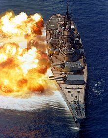 A large ship partially obscured by fire emanating from gun barrels pointed to the left.