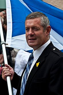 A middle-aged man wearing a suit and tie holding the Scottish flag.