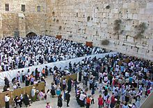 Two large groups of people, seen from slightly above them, separated by a white cloth barrier, standing before a beige stone wall whose top cannot be seen, with another wall in the rear. The group in the foreground is all female, the one in the rear is all male, with many wearing white robes or shrouds
