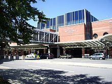 """Three-story brick building with blue windows; a glass pedestrian bridge travels from building to unseen parking garage on left, crossing entrance road. """"ALBANY INTERNATIONAL AIRPORT"""" sign is visible on side."""