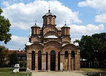 Exterior of the Gračanica monastery from the front, showing the tall and narrow central drum and dome and two of the four tall and narrow corner drums and domes of the square plan