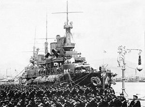 A black and white picture of a ship at anchor with uniformed men to the ship's left side.
