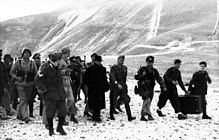 line of German soldiers walking with Mussolini
