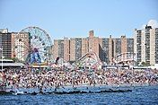 Crowded Coney Island beach with ferris wheel and roller coaster in background
