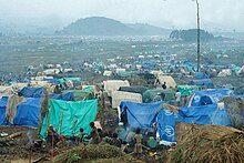 起雾时的难民营,可见各种颜色的帐篷和居住于此的难民。
