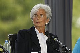 A three-quarter portrait of an elegantly dressed Christine Lagarde, perhaps in her early 60s sitting in a chair behind a microphone. She looks fit and tanned. Her overall mien is alert, pleasant, and intelligent.