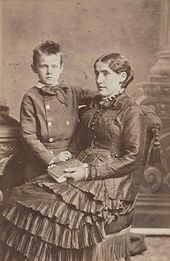 A young woman facing left sits with a child to her right