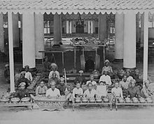 large group of musicians in Javanese costume, with percussion instruments