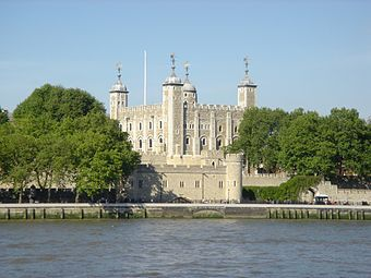 A huge square tower of grey stone is seen beyond fortifications on the edge of a river.
