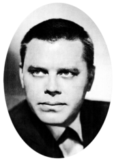A dark-haired man with a neutral expression wearing a dark jacket