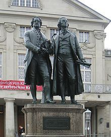 """Photograph of a large bronze statue of two men standing side by side and facing forward. The statue is on a stone pedestal, which has a plaque that reads """"Dem Dichterpaar/Goethe und Schiller/das Vaterland""""."""