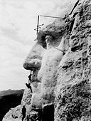 Profile of stone face jutting out from a mountainside. Three workers clamber over it, each about the height of the face's upper lip.
