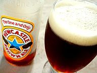 """A wide Geordie schooner glass with a stem, filled with dark brown beer with a large foam head. Next to it is a mostly-empty bottle labelled """"The One and Only: Newcastle Brown Ale"""""""