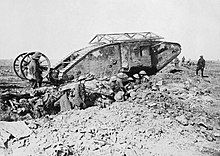 Early First World War tank, with soldiers in a trench next to it