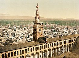 A color photochrom cityscape of 19th-century Damascus, showing a tower rising over an arcade in the forefront, old buildings in the background and gardens and hills on the horizon