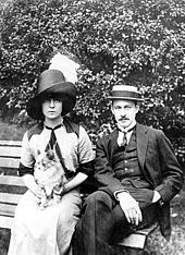 Barrymore and Katherine Corri Harris sitting on a park bench, both wearing jaunty hats and looking at the camera