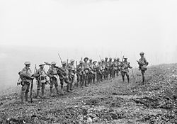 A line of soldiers in battle equipment face another soldier who is addressing them on a gentle slope. Behind them smoke or fog obscures the rest of the terrain