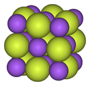 Checkerboard-like lattice of small blue and large yellow balls, going in three dimensions so that each ball has 6 nearest neighbors of opposite type