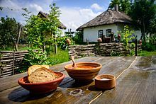 A meal of borscht and bread on a wooden table standing in the yard of a traditional peasant hut