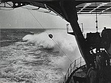 Photograph taken on board a ship that shows part of the stern and also the ocean behind the ship. The horizon is in the distance, and there is a large wake behind the ship. The photograph shows a lower deck of the ship as well as the support structure and the bottom of an upper deck. There are about six members of the crew visible at the back of the lower deck who are dwarfed by the ship's structures.