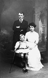 A studio portrait. A young man stands with his arms folded; he has dark hair, and is wearing a dark Edwardian suit, a white shirt with rounded collars, and a dark tie, To his right, a young woman sits on a wooden bench; she has dark, medium length hair, and is wearing a white blouse and a long white skirt. She holds a young fair-haired boy, who is wearing a light tunic with flared skirt and embroidery at the neck, dark boots and short socks. He holds a walking stick in his right hand. An empty paint tin lies on its side near his feet. The background has a colonnade and clouds in the classical romantic style.