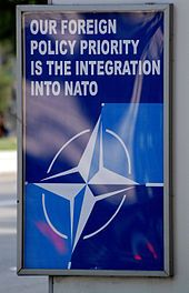 """A blue poster at a bus stop with the NATO logo and the words """"OUR FOREIGN POLICY PRIORITY IS THE INTEGRATION INTO NATO"""" in white."""