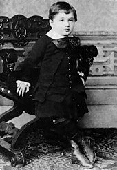 A young boy with short hair and a round face, wearing a white collar and large bow, with vest, coat, skirt, and high boots. He is leaning against an ornate chair.