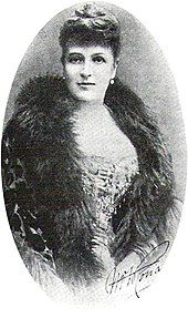 """Photo of Ronalds from the waist up, facing the camera. She is handsome and well-dressed, with a fur collar and an """"up"""" hairdo."""
