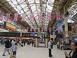 Victoria station concourse. British flags hang from the ceiling.