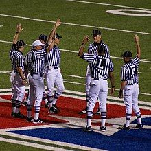 Seven officials are pictured meeting at the infield. Officials meeting at midfield