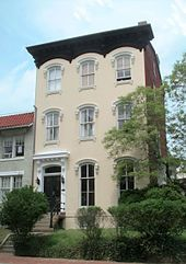 A yellow three-story townhouse with steps in front and a small lawn with shrubs and trees.