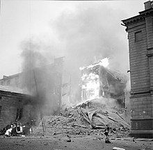 An apartment building is on fire and has partly collapsed in Central Helsinki after Soviet aerial bombing on 30 November 1939. A woman in a coat and a hat is passing on the right next to the rubble and a car is on fire on the left.