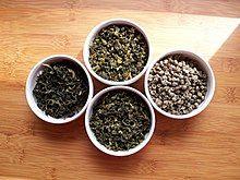 Four small white bowls of tea