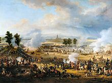 A crowded scene with many soldiers and horses, and much smoke. Some soldiers lie dead or wounded. In the distance, beyond a short line of trees, is a tall church tower.