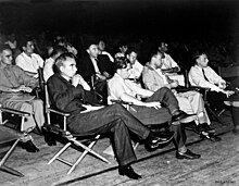 一群身穿衬衫的男子坐在折叠椅里,面朝一个方向,聚精会神。