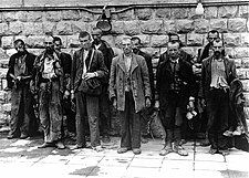Several men standing in front of a brick wall.