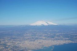 An aerial view of the Metropolitan City around Catania. Mt. Etna is the peak at a distance.