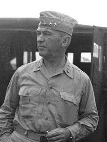 Man in garrison cap and open necked shirt, both sporting sets of three stars.