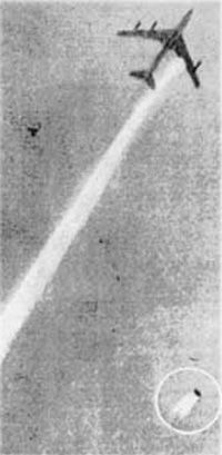 A photograph of an aircraft in flight, with an engine falling to earth