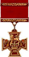 A bronze cross pattée bearing the crown of Saint Edward surmounted by a lion with the inscription Pro Valore. A Bar crosses the crimson ribbon attached to the medal.