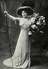 Woman standing in a dramatic pose, right arm raised, left arm holding a large bouquet. She is wearing a long formal gown and a wide-brimmed hat.