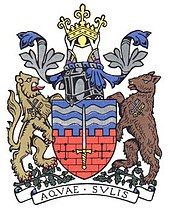 Coat of arms showing a shield with two silver wavy lines on a blue background and a brick wall with battlements. In the centre of the shield is a sword. On either side of the shield are a lion and a bear standing on a bed of acorns. Above them is a knight's helmet and crown.