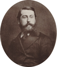 Middle aged white man with short, dark hair and a bushy beard
