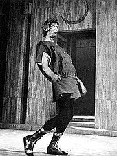 A tall figure in a tunic, black trousers and boots, wearing a laurel wreath and a pop-eyed expression, is moving from left to right in an exaggerated pose, head back and midriff thrust forward. In the background are steps leading to a door.